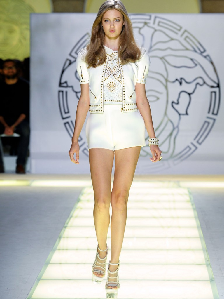 Versace Fashion Runway Show With Beautiful Versace Models Modeling Versace White Shorts And White Heels On The Fashion Runway.